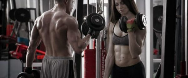 Couple doing dumbell curls at gym to build muscle fast