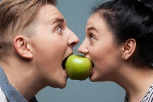 Man and woman bitng an apple posing for best weight loss supplements