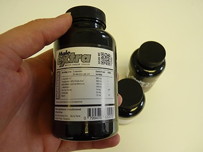 Maleextra bottle with ingredients being shown in left hand